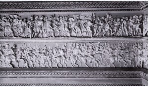 Two rows of a frieze depicting many people fighting in battle; the bottom row features people primarily on horseback.