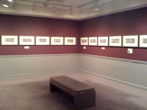 A gallery with gray and red walls depicting a series of small engravings all lined up in a single row.