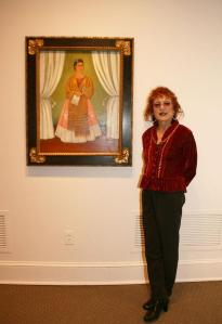 Judy Chicago next to Frida Kahlo's Self-Portrait Dedicated to Leon Trotsky, 1937, in NMWA's collection galleries